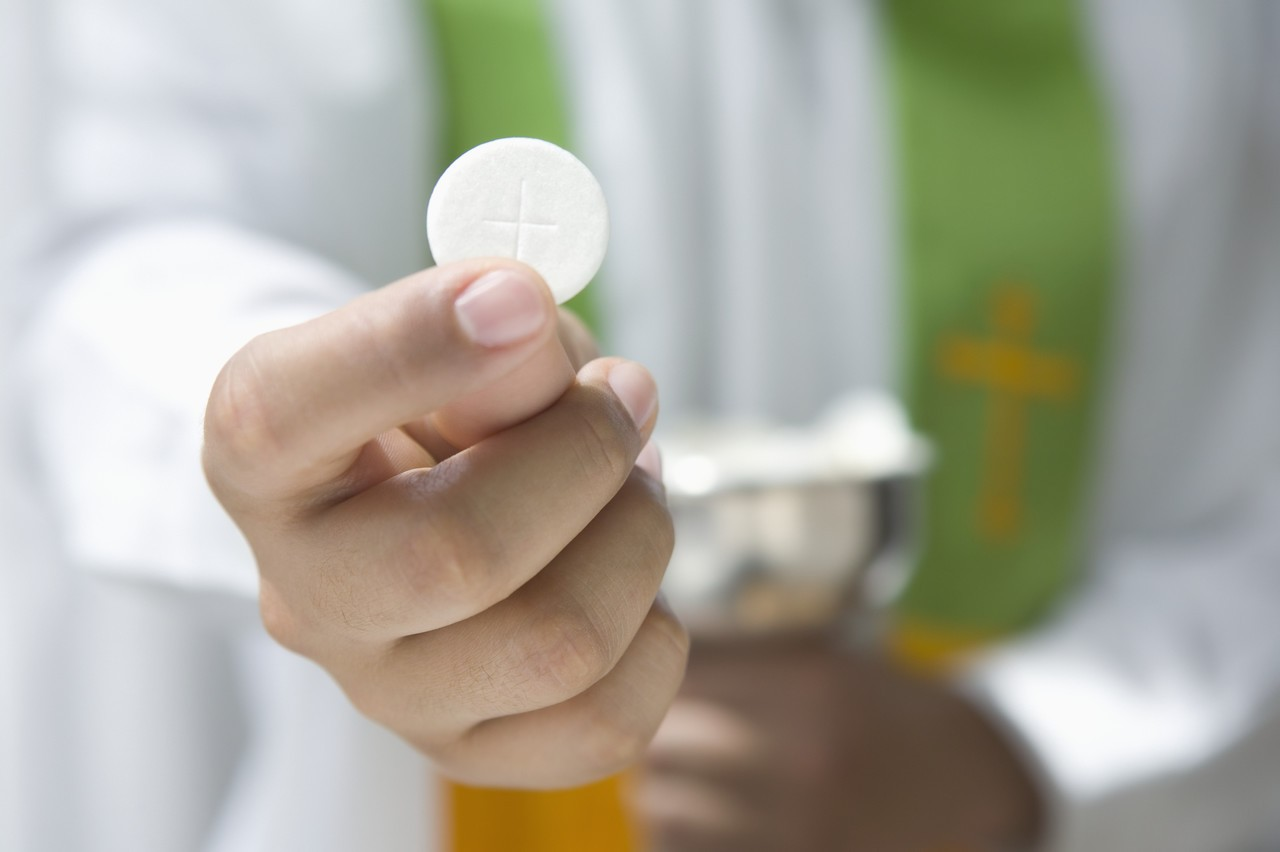 Priest Holding Communion Wafer --- Image by © Royalty-Free/Corbis